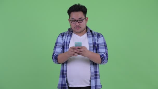 Happy young overweight Asian hipster man thinking while using phone
