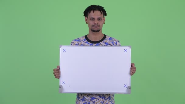 Stressed young African man holding white board
