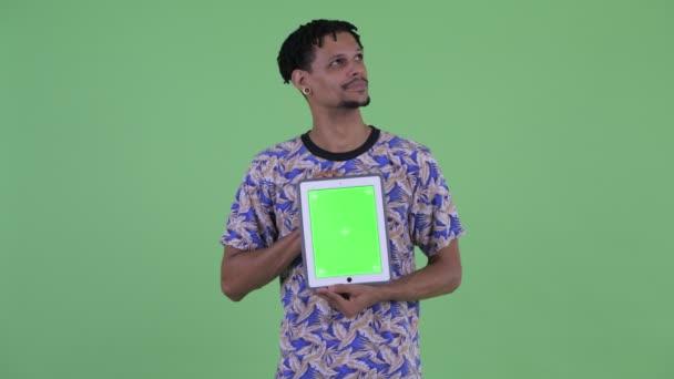 Šťastný mladý pohledný Afričan přemýšlí, když zobrazuje digitální tablet