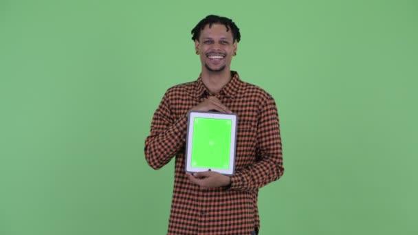 Veselý mladý pohledný Afričan, který mluví s digitálním tabletem