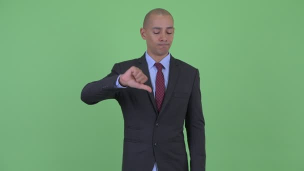 Angry bald multi ethnic businessman giving thumbs down