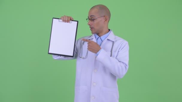 Šťastný holohlavý multietnický lékař zobrazující schránku a dává palce