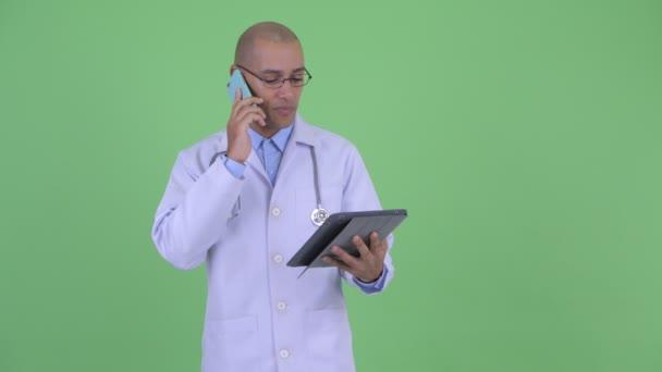 glücklich glatzköpfige multiethnische Mann Arzt mit digitalem Tablet und telefonieren