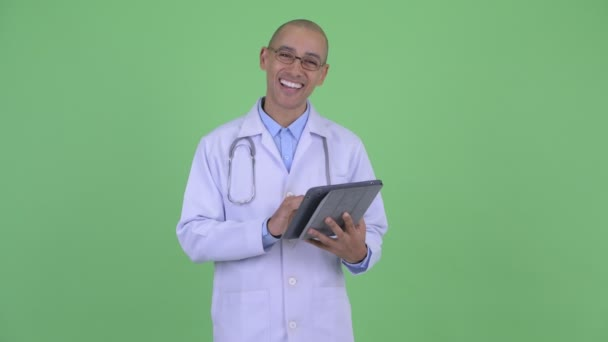 Happy bald multi ethnic man doctor talking while using digital tablet