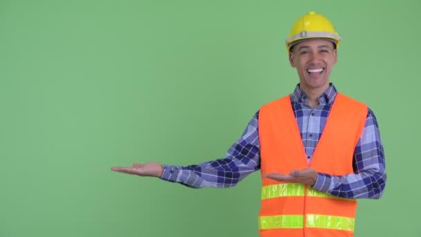 Šťastný dělník multietnického muže ukazující něco