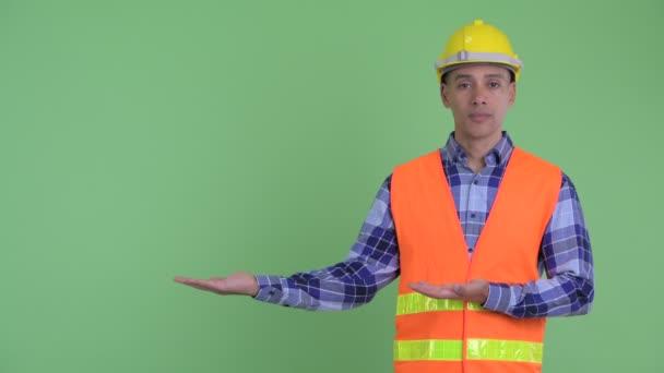 Zdůrazňoval stavební pracovník multietnického muže, který ukazuje něco