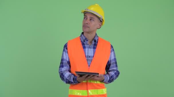 Šťastný víceetnický stavební pracovník při používání digitálního tabletu