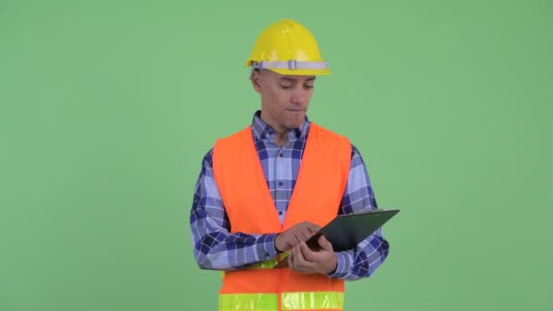 Happy multi ethnic man construction worker holding clipboard and pointing finger