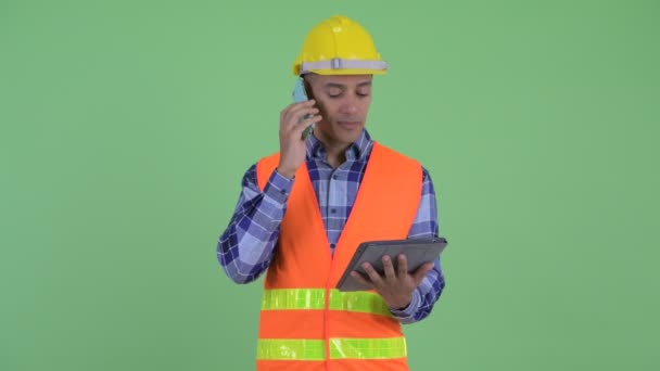 Šťastný stavební pracovník pro více etnických mužů, který mluví na telefonu při používání digitálního tabletu
