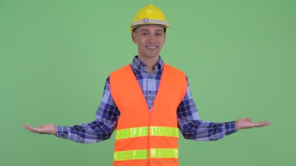 Šťastný stavební pracovník pro více etnických mužů porovnávající něco