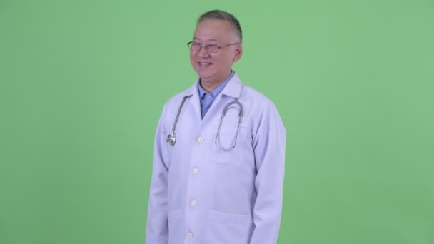 Happy mature Japanese man doctor thinking