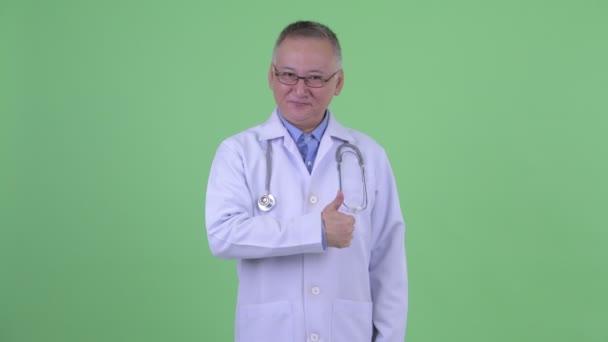 Šťastný dospělý japonský doktor, který dává palce