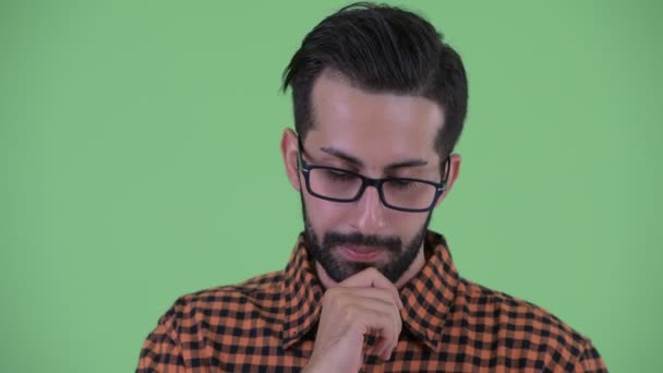 Face of stressed young bearded Persian hipster man thinking and looking down
