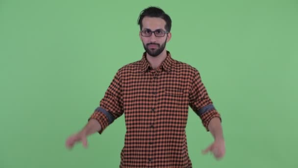 Happy young bearded Persian hipster man with hand heart gesture
