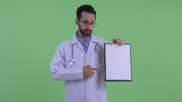 gestresster junger bärtiger persischer Mann Arzt zeigt Klemmbrett und gibt Daumen nach unten