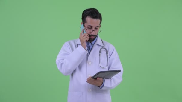 glücklicher junger bärtiger persischer Mann Arzt telefoniert und nutzt digitales Tablet