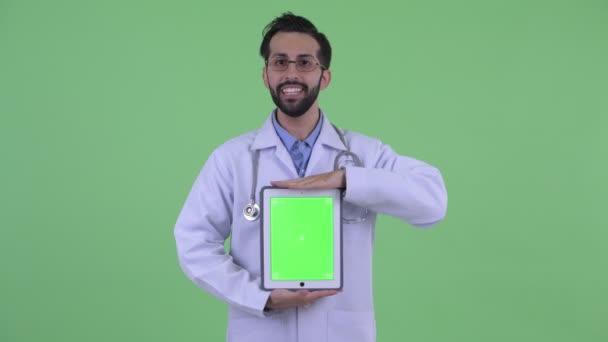 glücklicher junger bärtiger persischer Mann Arzt spricht, während er digitales Tablet zeigt