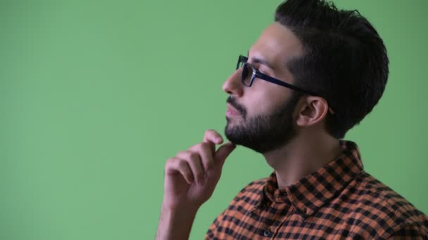 Closeup profile view of happy young bearded Persian hipster man thinking