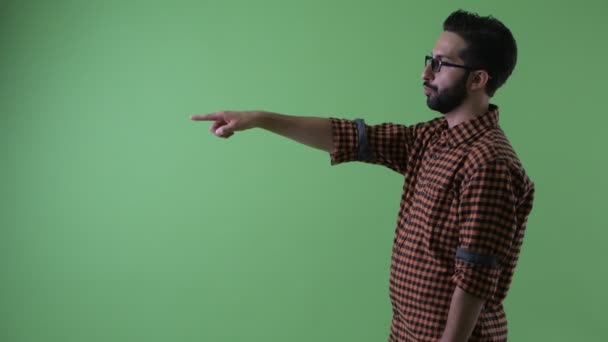 Profile view of happy young bearded Persian hipster man pointing finger