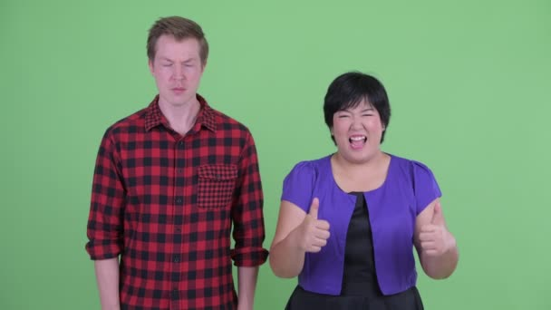 Happy overweight Asian woman giving thumbs up with Scandinavian hipster man looking confused