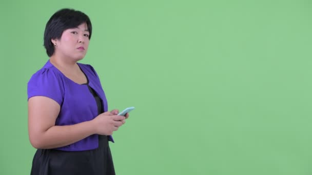 Happy young overweight Asian woman waiting while using phone