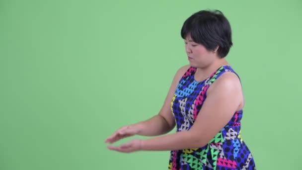 glücklich junge übergewichtige asiatische Frau schnippt die Finger und zeigt etwas