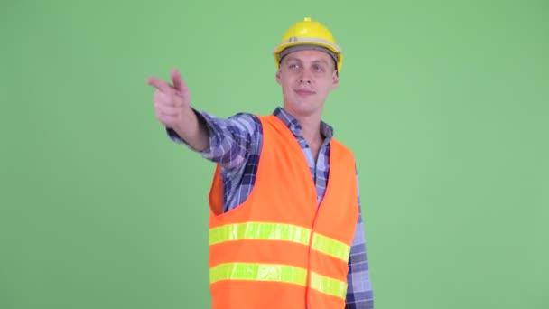 Šťastný stavební pracovník, který dává palce