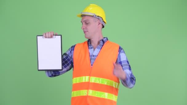 Šťastný dělník mladých mužů zobrazující schránku a dává palce