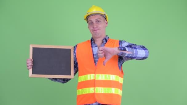 Zdůraznil mladý stavební pracovník, který drží tabuli a dává palce