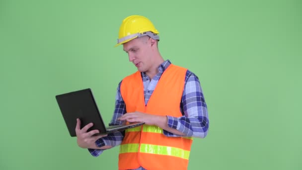 Spokojený mladý stavební pracovník při používání přenosného počítače