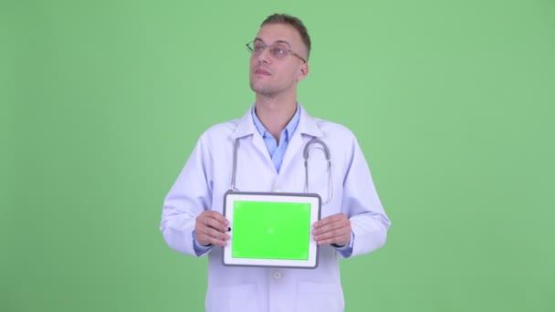 Šťastný fešák doktor přemýšlí, když zobrazuje digitální tablet