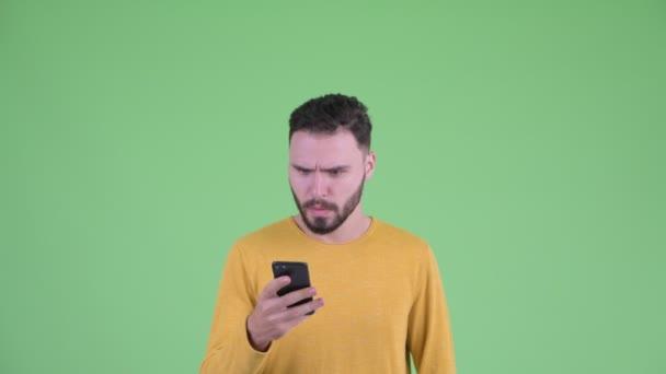 Gesicht eines glücklichen jungen bärtigen Mannes, der sein Telefon benutzt und überrascht aussieht