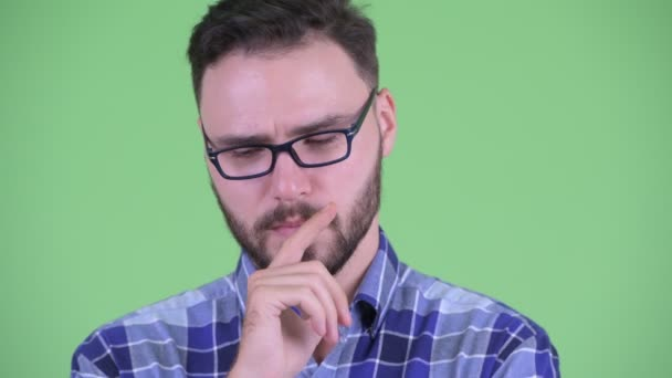 Face of stressed young bearded hipster man thinking and looking down