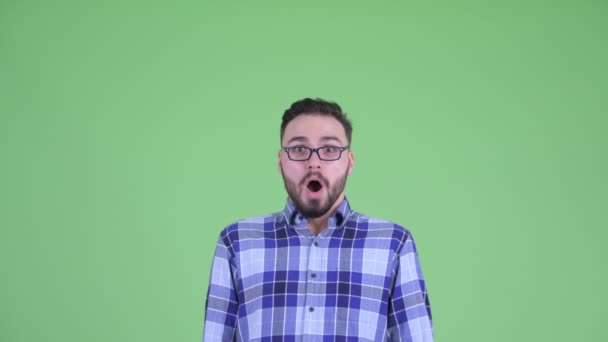 Face of young handsome bearded hipster man looking shocked