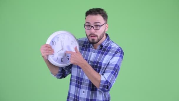 Vicces hangsúlyozta a fiatal szakállas csípő ember mutatja óra és azt mondja, hogy hagyja abba
