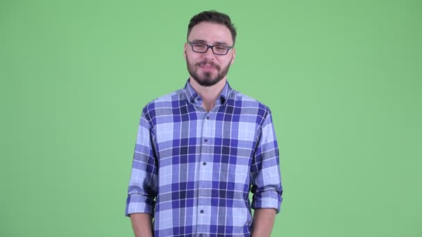 Happy young bearded hipster man talking to camera