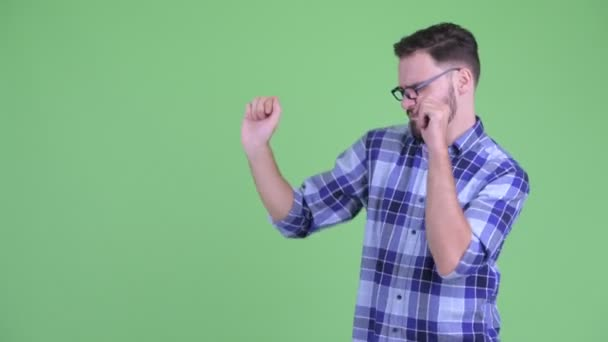 Happy young bearded hipster man touching something and dancing