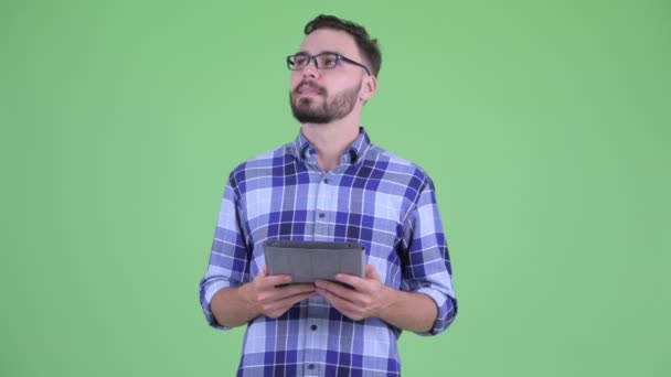 Happy young bearded hipster man thinking while using digital tablet