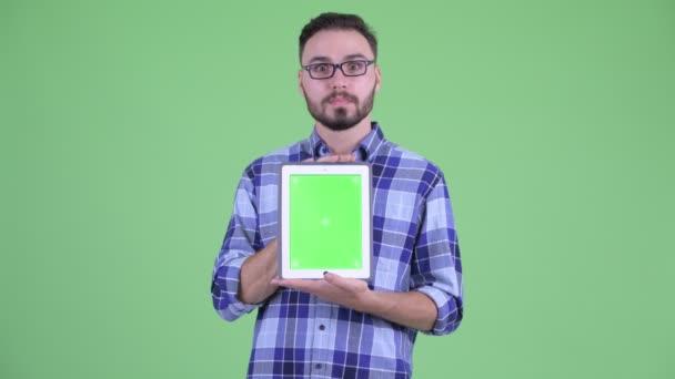 Glücklicher junger bärtiger Hipster-Mann zeigt digitales Tablet und wirkt überrascht