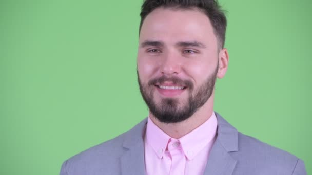 Face of happy young handsome bearded businessman thinking