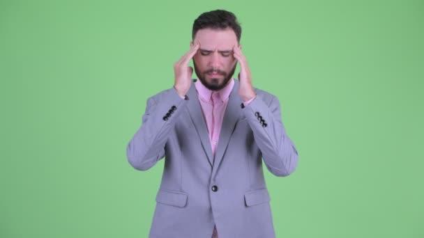 Stressed young bearded businessman having headache