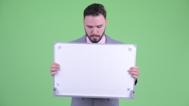 Stressed young bearded businessman holding white board and getting bad news