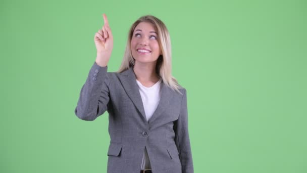 Happy young beautiful blonde businesswoman pointing up