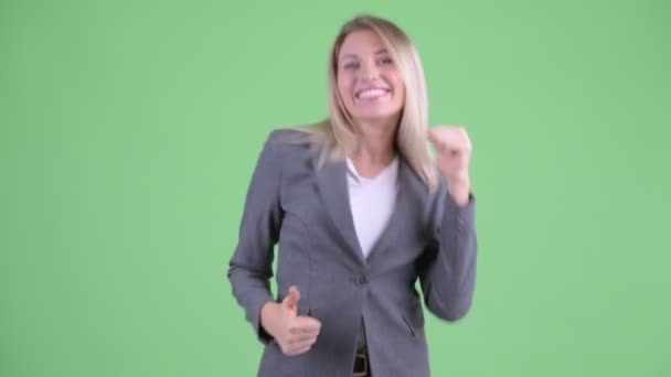 Happy young blonde businesswoman giving thumbs up and looking excited