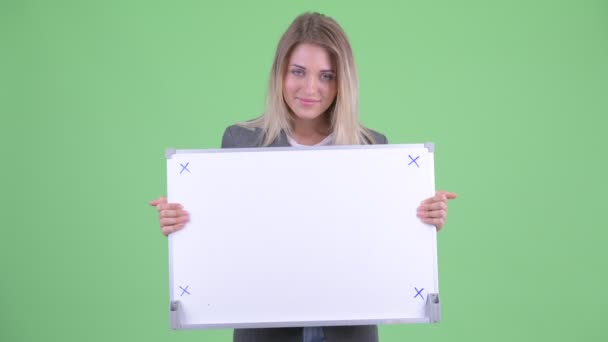 Happy young blonde businesswoman holding white board and getting good news