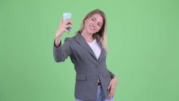 Happy young blonde businesswoman taking selfie and video calling