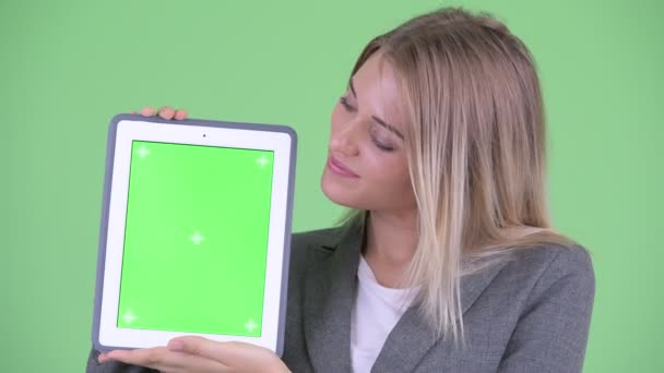 Face of happy young blonde businesswoman showing digital tablet