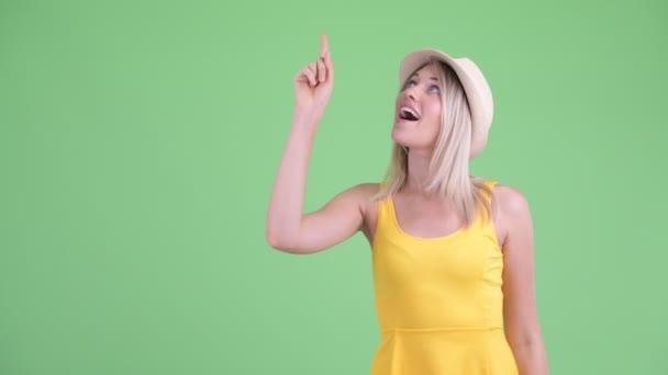 glückliche junge blonde Touristin zeigt nach oben und sieht aufgeregt aus