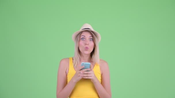 glückliche junge blonde Touristin telefoniert und sieht überrascht aus