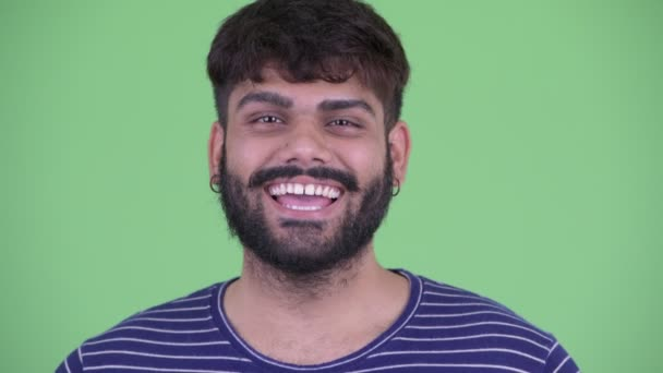 Face of happy young overweight bearded Indian man smiling